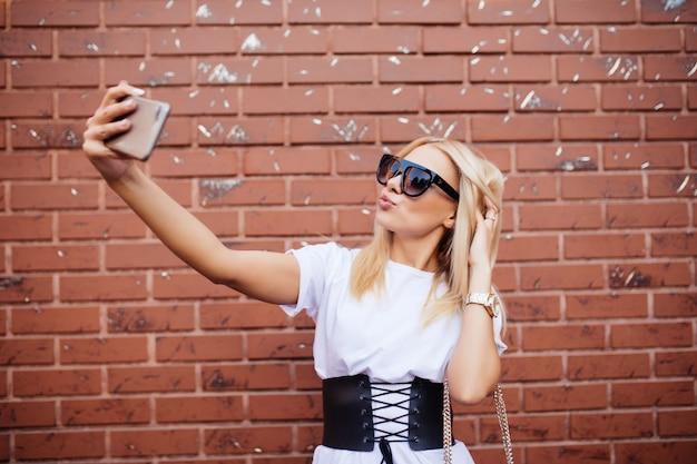 Mooie blonde blanke vrouw staande voor bakstenen muur en selfie maken.