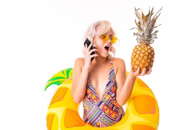 Mooie blonde blanke vrouw staat in zwembroek met rubberen strand ananas ring, praat aan de telefoon en kijkt naar de ananas geïsoleerd op witte achtergrond