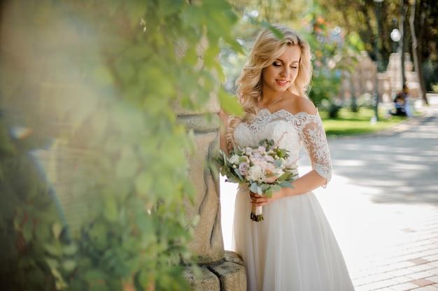 Mooie blonde bruid gekleed in een mooie jurk