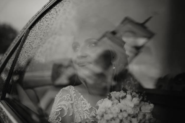 Mooie blonde bruid in de auto