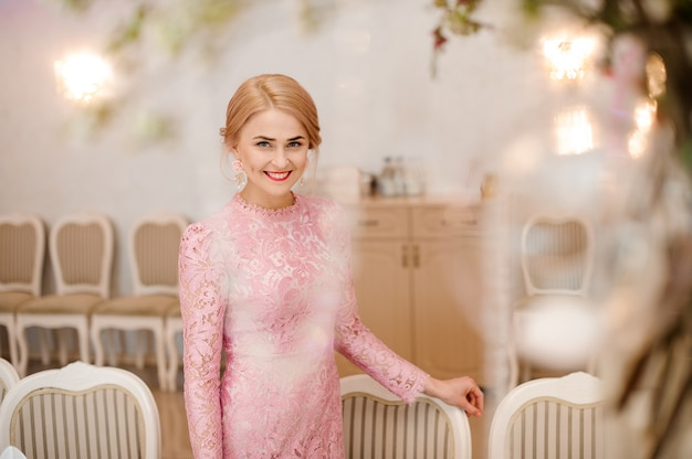 Mooie blonde bruid in prachtige roze jurk