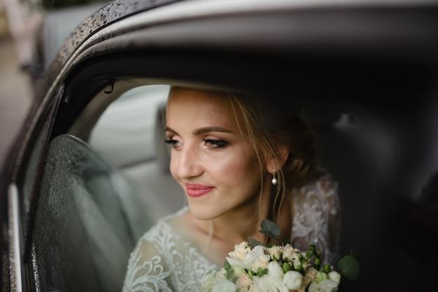 Mooie blonde bruid kijkt uit het autoraam. regenachtig weer.