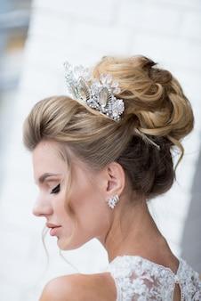 Mooie blonde bruid met hoog kapsel en kostbare zilveren kroon op haar haar