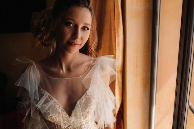 Mooie blonde bruid met mooieen mooie bruid met aangename eigenschappen in een trouwjurk vormt in het interieur van de kamer.