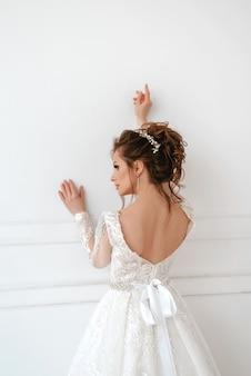 Mooie blonde bruid op witte muur