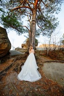 Mooie blonde bruid staat met haar rug