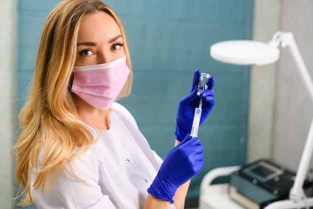 Mooie blonde cosmetologie arts in roze wegwerp gezichtsmasker en blauwe rubberen handschoenen
