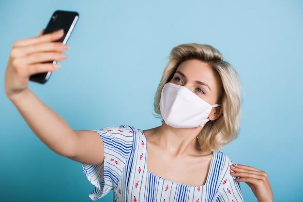 Mooie blonde dame met medisch masker op gezicht maakt een selfie met behulp van een telefoon op een blauwe studiomuur