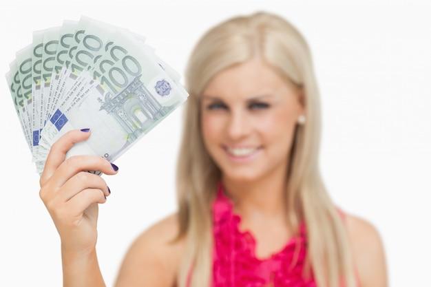 Mooie blonde die 100 euro bankbiljetten toont