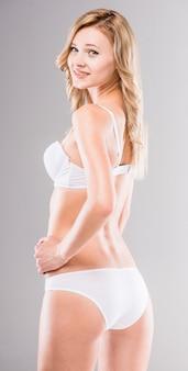Mooie blonde die in witte lingerie voorzijde bekijkt.
