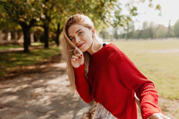 Mooie blonde die speels op de bosmuur kijkt. verbluffende vrouw die zich ontspannen voelt in de prachtige natuur.