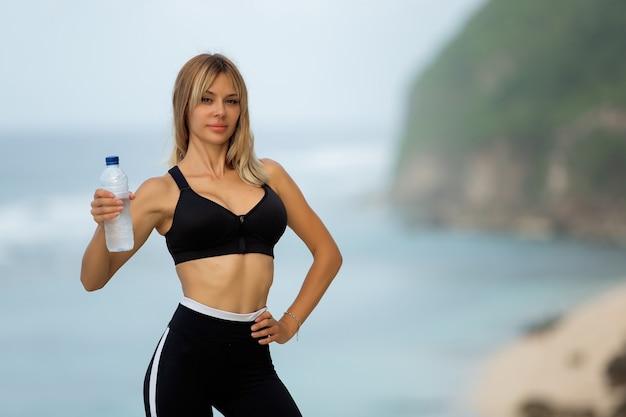 Mooie blonde drinkt water