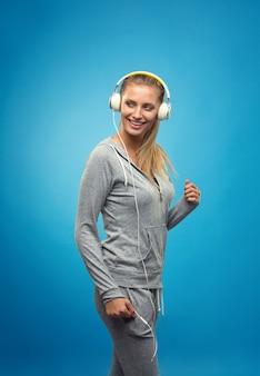 Mooie blonde fit blanke dame in grijze sport met koptelefoon luisteren muziek. geïsoleerd op blauwe muur