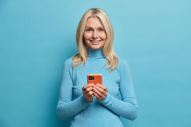 Mooie blonde gerimpelde vrouw overboekingen online geld houdt mobiele telefoon