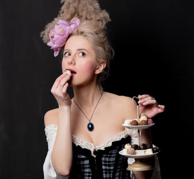 Mooie blonde gravin met chocoladesuikergoed Premium Foto