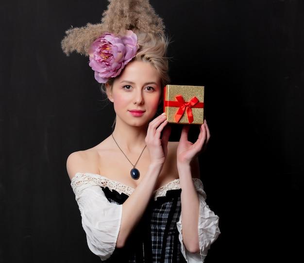 Mooie blonde gravin met een geschenkdoos Premium Foto