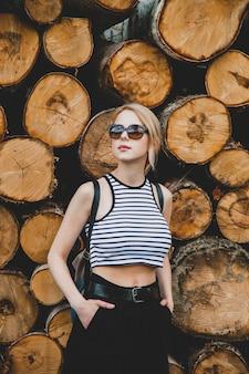 Mooie blonde haarvrouw in sungaases staat dichtbij boomstammen in een bos in