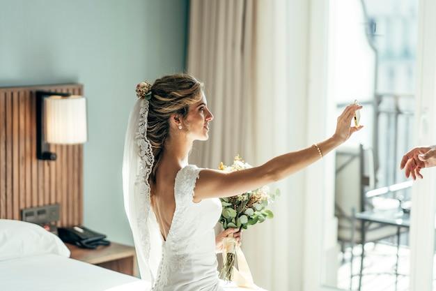 Mooie blonde harige vrouw gekleed in het wit op haar trouwdag voordat ze gaat trouwen, een foto van zichzelf maken.