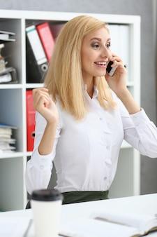 Mooie blonde het glimlachen cellphone van de onderneemsterbespreking