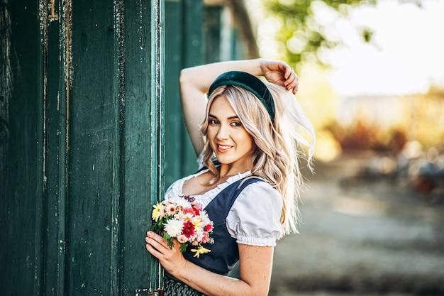 Mooie blonde in dirndl, traditionele oktoberfest jurk staande op de boerderij in de buurt van houten deur