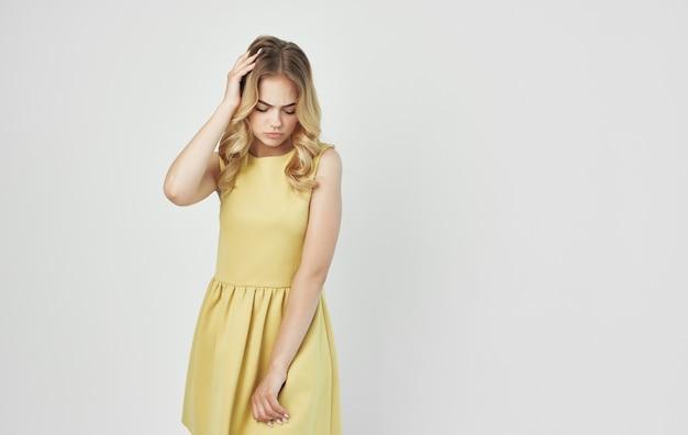 Mooie blonde in een gele jurk lichte muur aantrekkelijke uitstraling.