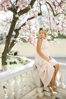 Mooie blonde in een lange jurk zit in de buurt van magnolia