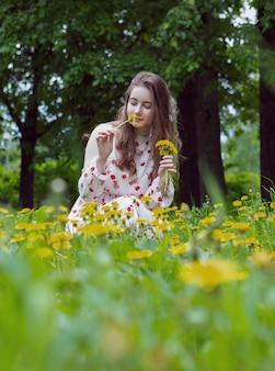 Mooie blonde in een lichte jurk verzamelt een boeket gele bloemen