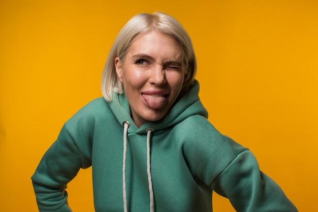 Mooie blonde in groene hoodie toont tong aan de camera op een gele achtergrond. hoge kwaliteit