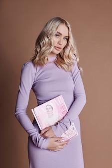 Mooie blonde in lange jurk leest ouderwetse tijdschriften op bruin