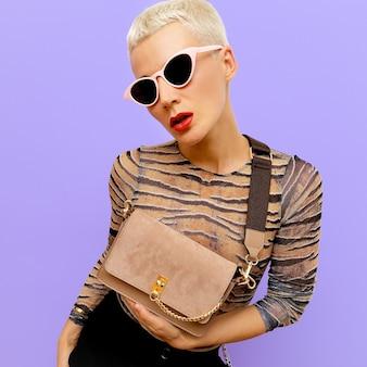 Mooie blonde in modeaccessoires zonnebrillen en clutch. accent voor beige en dierenprint