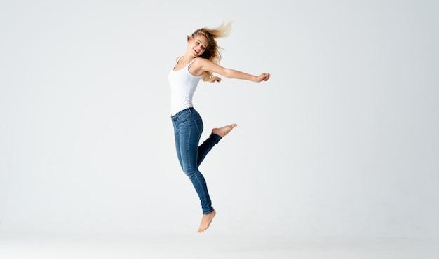 Mooie blonde in spijkerbroek staat blootsvoets op de vloer geïsoleerd achtergrondmodel