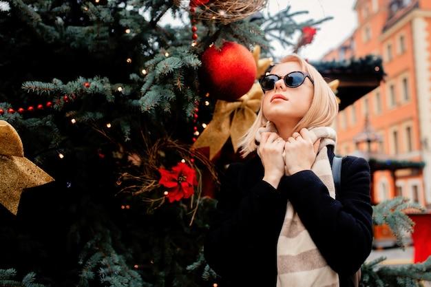 Mooie blonde in suglasses op de kerstmarkt in wroclaw, polen