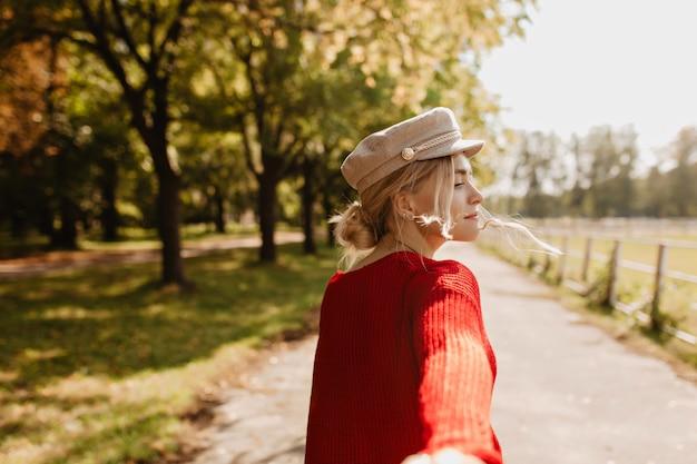 Mooie blonde in trendy kleding die speels vraagt om haar te volgen in het park. mooi meisje genieten van zonnig weer buiten.