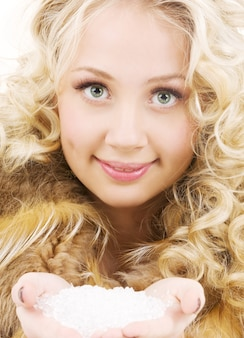 Mooie blonde in vacht met een handvol ijs