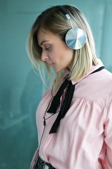 Mooie blonde in zilveren koptelefoon luistert naar muziek