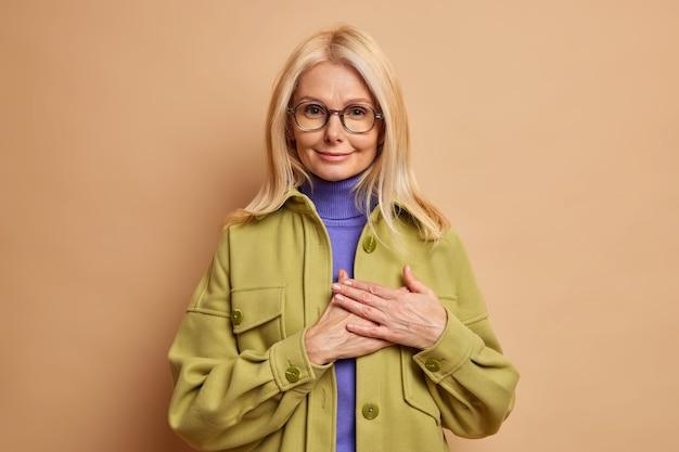 Mooie blonde jonge europese vrouw maakt dankbaar gebaar wordt aangeraakt en staat dankbaar draagt modieuze jas.