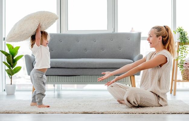 Mooie blonde jonge moeder zittend op de vloer en spelen met haar zoontje kind met kussen. gelukkig familieportret