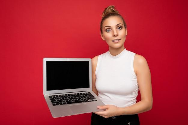 Mooie blonde jonge vrouw die de computerlaptop van de cameraholding bekijkt die wit t-shirt draagt