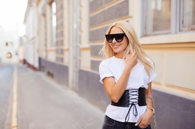 Mooie blonde jonge vrouw die in de stad loopt. mode.