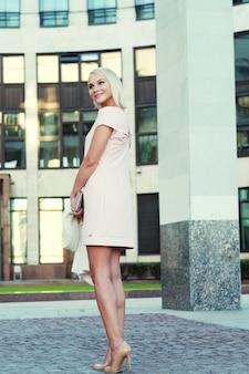Mooie blonde jonge vrouw die kleding draagt en op straat loopt
