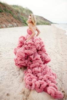 Mooie blonde jonge vrouw die roze kleding op het strand draagt