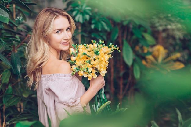 Mooie blonde jonge vrouw die zich dichtbij de installaties bevindt die gele fresia houden