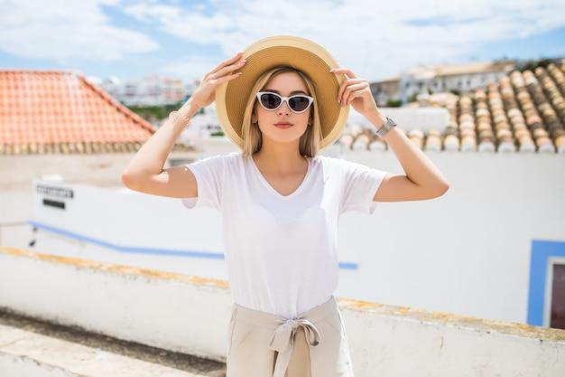 Mooie blonde jonge vrouw met hoed en zonnebril lopen op straat