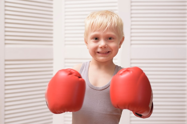 Mooie blonde jongen in rode bokshandschoenen. sport