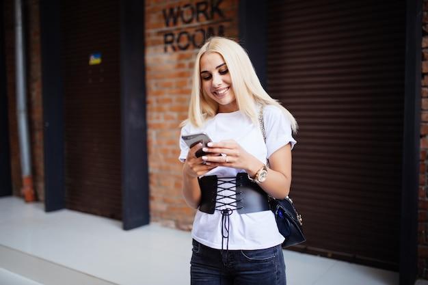 Mooie blonde kaukasische vrouw met hoofdtelefoon die zich voor bakstenen muur bevindt die een sms-bericht typt en geniet in haar favoriete koffie.
