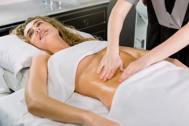 Mooie blonde krullende vrouw die lacht, liggend op het bed en maagmassage heeft. lichaamsverzorging, medisch kuuroord.