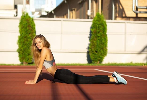 Mooie blonde langharige sportieve model oefenen in de tennisbaan
