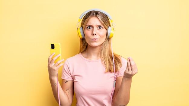 Mooie blonde meid die capice of geldgebaar maakt en zegt dat je moet betalen. luisteren muziek concept