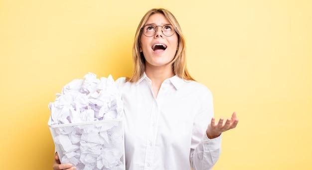 Mooie blonde meid die er wanhopig, gefrustreerd en gestrest uitziet. papier ballen prullenbak concept
