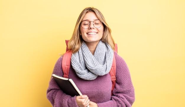 Mooie blonde meid die hardop lacht om een of andere hilarische grap. studentenconcept